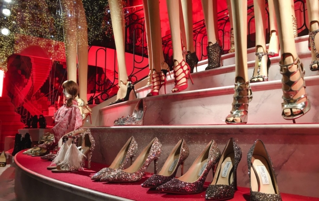 Different models of glittery shoes, golden, silver, red and black, strategically placed in the New Year's Eve window display.
