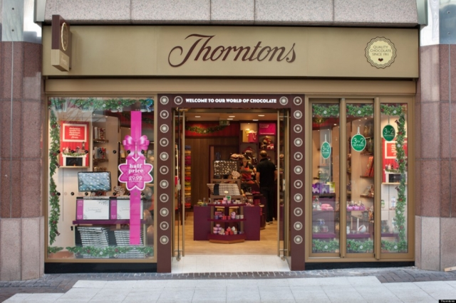 Simple and with good taste, this window display, has some fir branches as decoration and a pink bow sticker informing about the half price.
