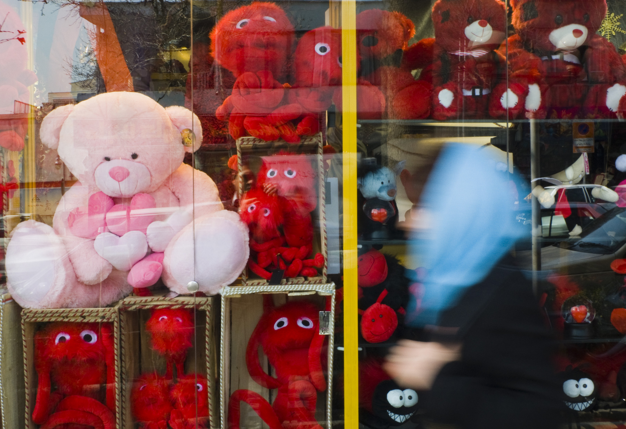 A Valentine's Day window display decorated only with plush, red teddy bears and one big pink teddy bear.