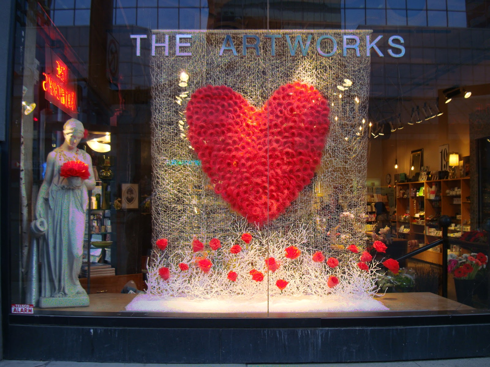 A window display for Valentine's day designed with fine taste, a statue holding flowers, and a beige background with a big heart in the middle and poppy flowers at the bottom.
