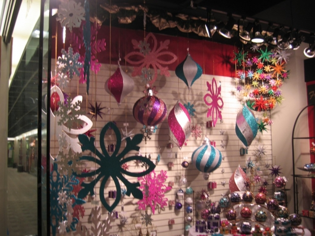 A window display that is sliding into the New Year's Eve with large sparkling ornaments in different colors.