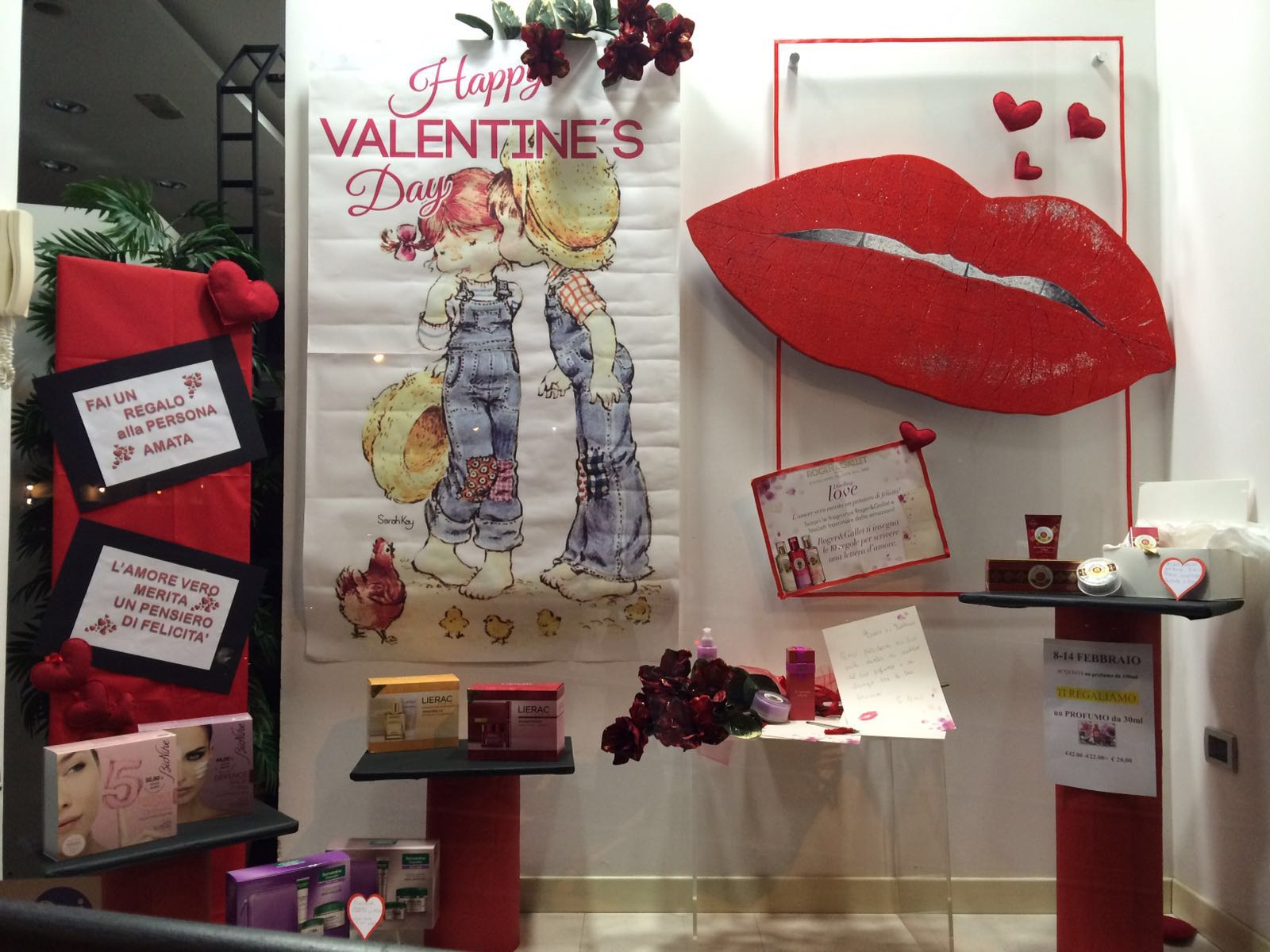 Red details in this pharmacy window display and a frame with some big lips on the background, designed for Valentine's day.