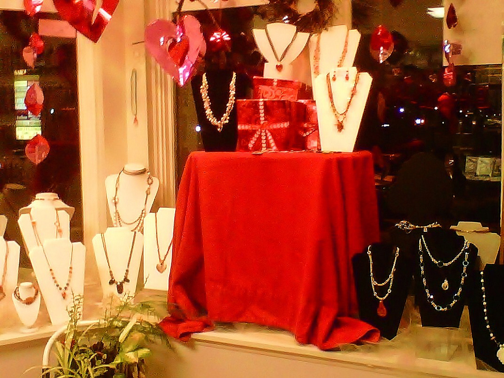 A Valentines' Day window display with jewelry, red objects, and hanging hearts.