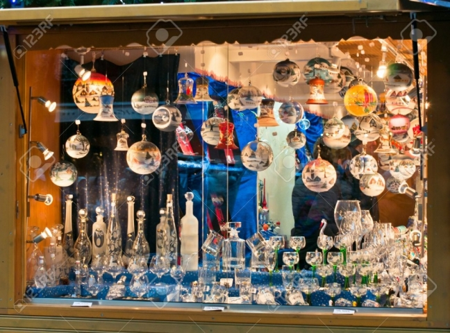A New Year's Eve window display full of spheres with different themes, glasses, and bottles.