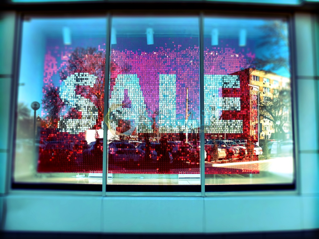 For the New Year's Eve window display, this store announces the sales through a sign made from many little glittery squares with red and silver.
