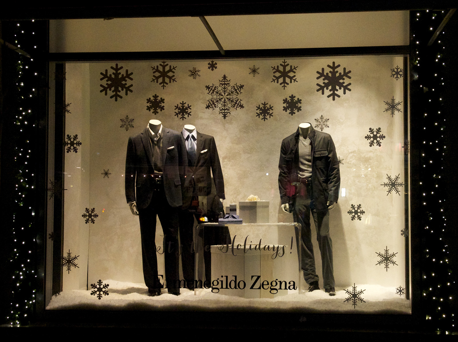 A stylish New Year's Eve window display, because of the classic men costumes, snow on the floor and the black frame with lights.