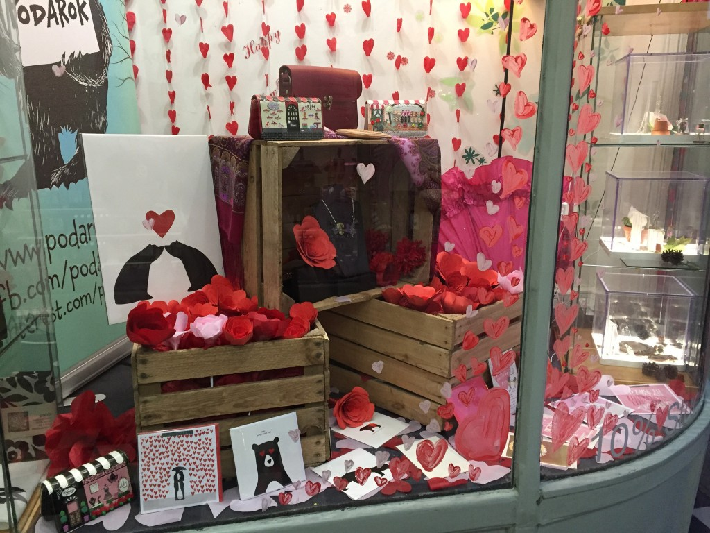 A lot of roses and red objects, also cards for Valentine's day in this window display.