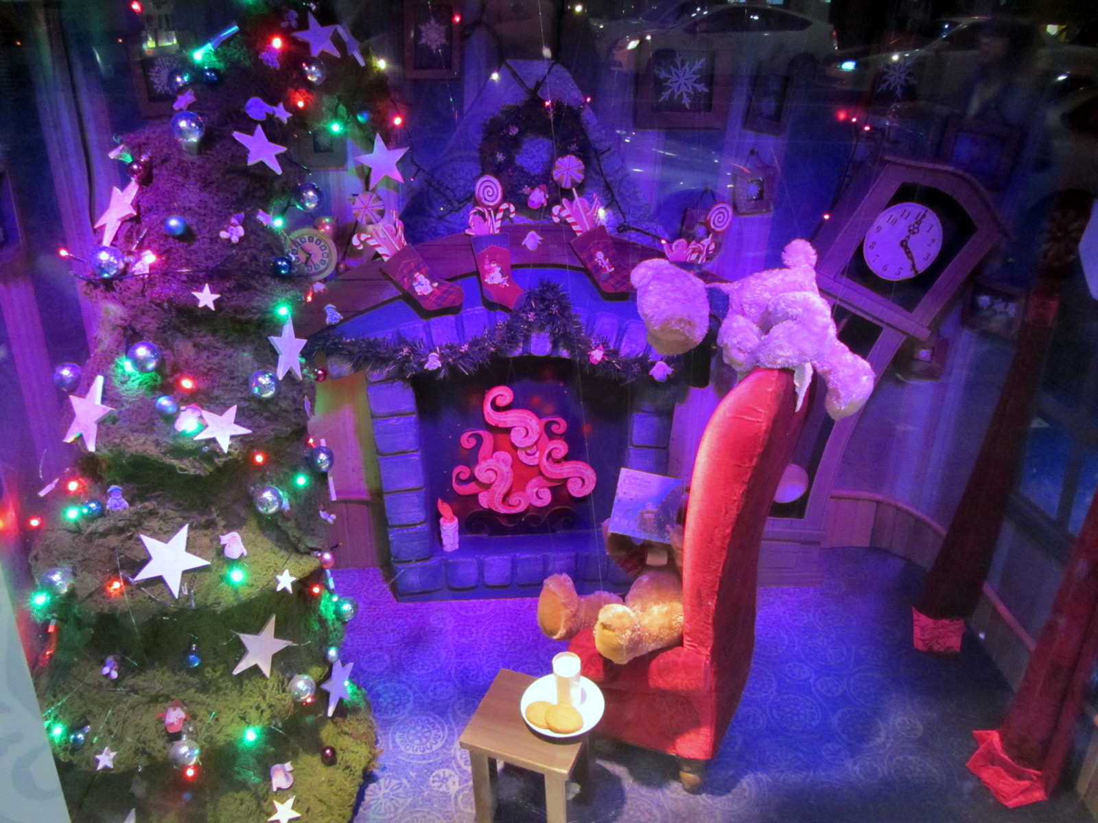 A window display, which describes a typical Christmas night, with some teddy bears waiting for Santa with milk and cookies near the adorned tree.