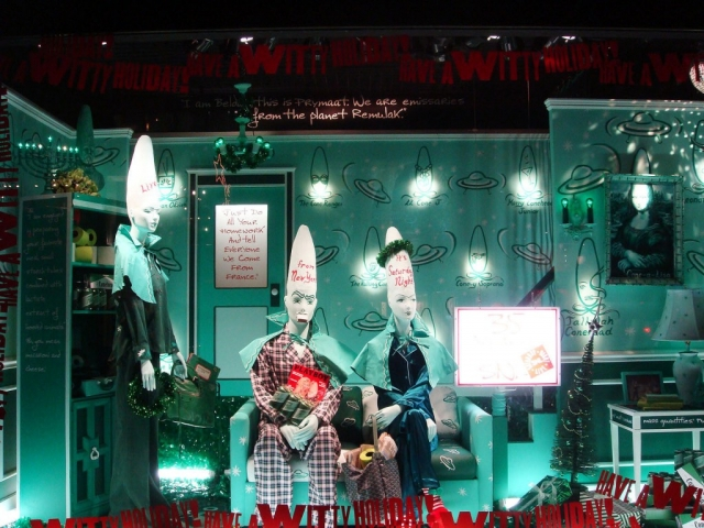 An extraterrestrial experience in this New Year's Eve window display, with ufo drawn on the wall, green lights, and mannequins with a big head.