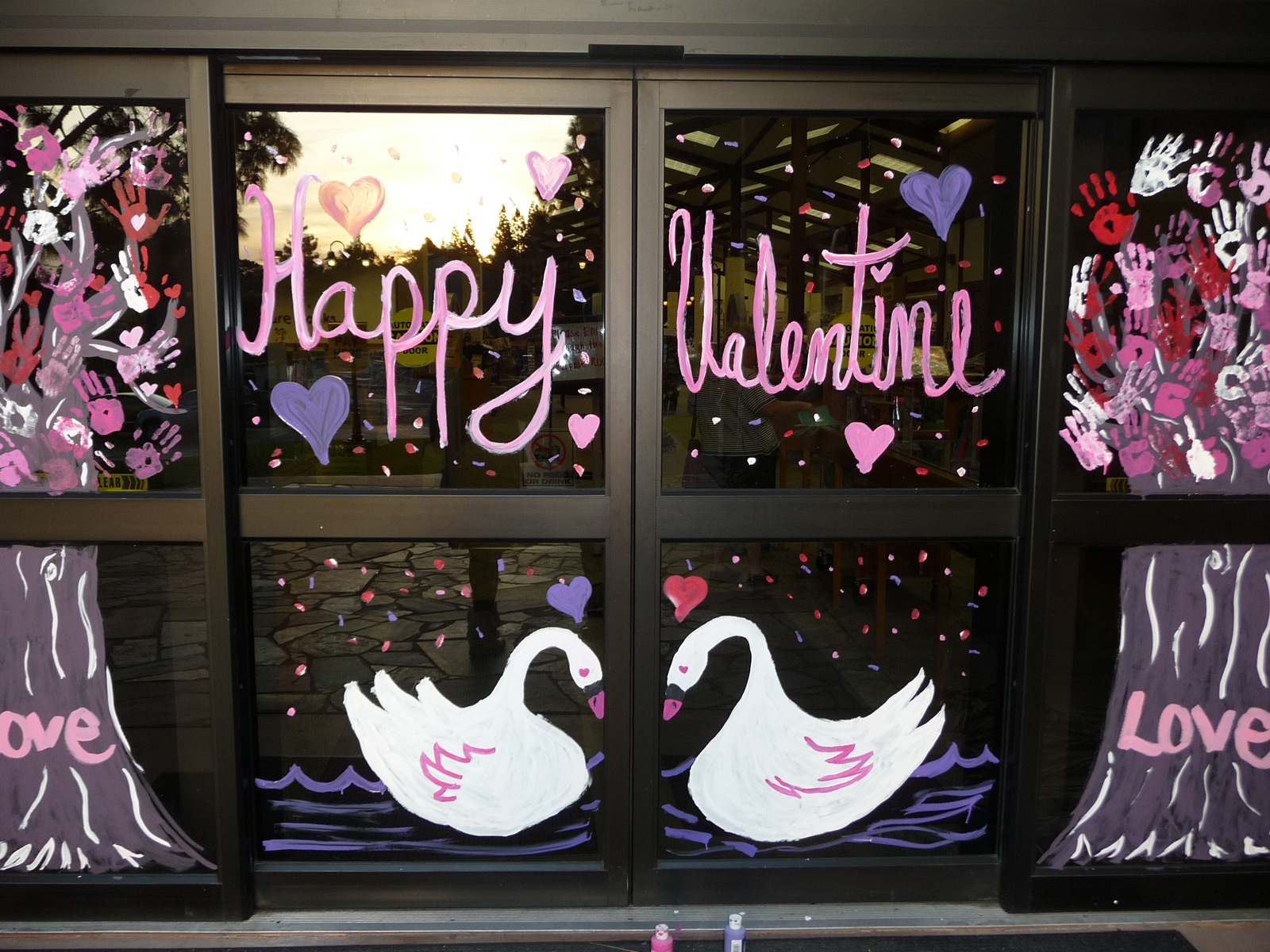 A window display with painted trees with palms instead of leaves and white swans symbolizing love on Valentine's day.