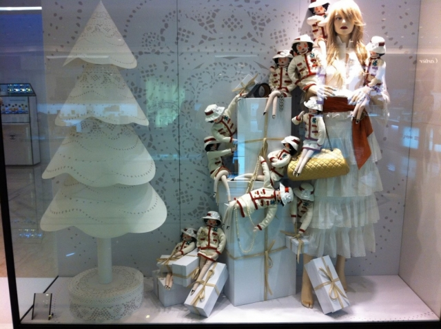 Cute white paper tree with lace model, and many little Coco Chanel dolls, are truly inspiring elegance for a New Year's Eve window display.