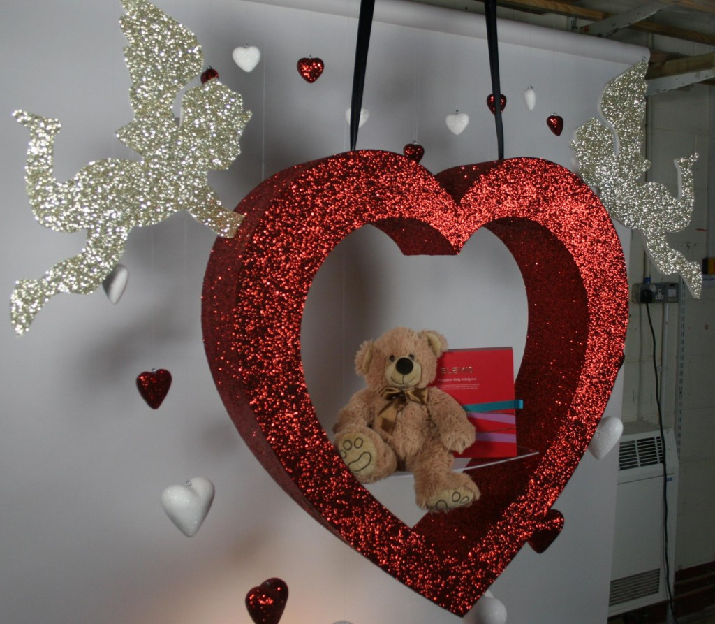 Two cupids holding a glitter heart, and a sweet teddy bear in the middle of it, a good decor for Valentine's Day window display.