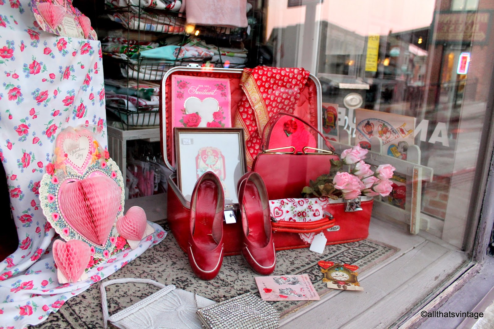Celebrating Valentine's day through this vintage decoration for the window display, with a red luggage with roses and other stuff, a red pair of shoes, a cute patterned fabric and other little details.