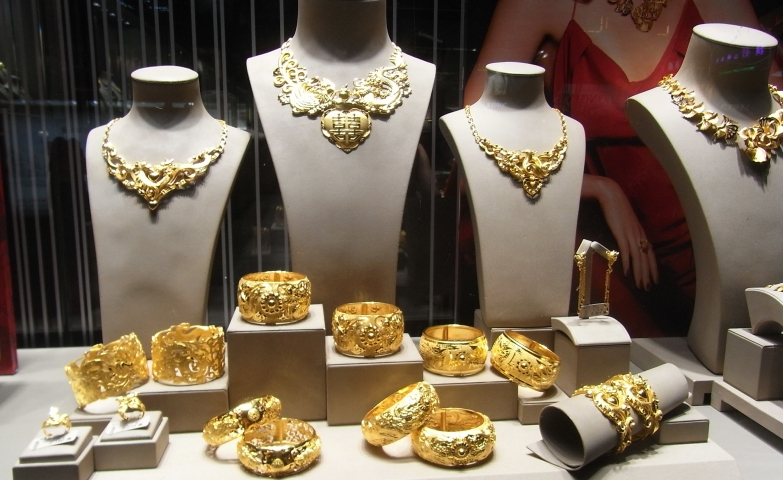 A minimalist, fashionable jewelry window display focused mostly on over-sized gold bangles, using classic jewelry stands and mannequin busts.