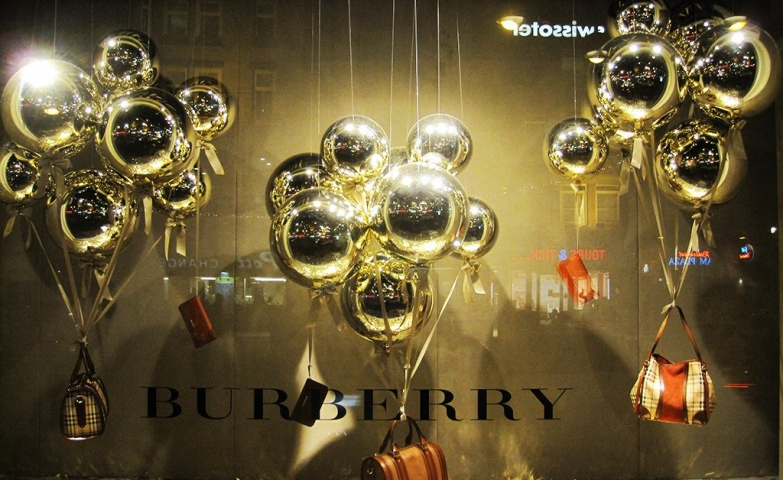 Burberry has three sets of golden balloons for Christmas window display, all of them carrying a purse.