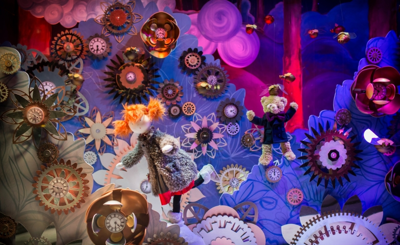A colored Christmas window display, with a cute doll and a plush bear in a playful environment.