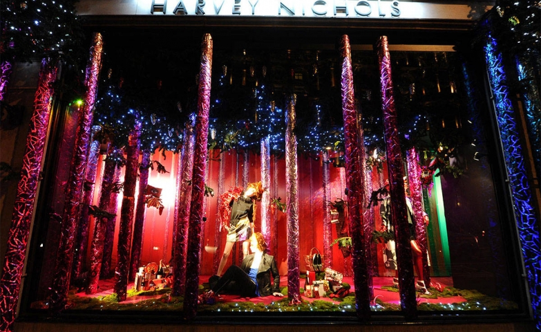 Mannequin between red piles and blue lights at Harvey Nichols Christmas window display.