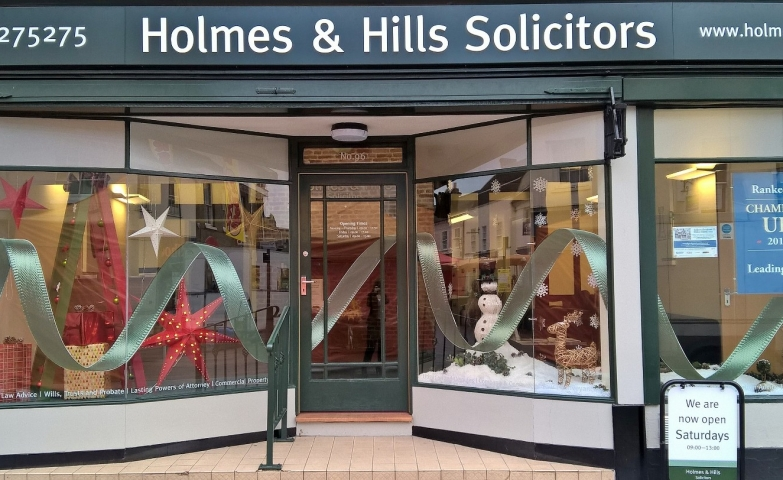 Holmes & Hills Solicitors has chosen not to cut the fir for Christmas and made one from a scale, also they added all over the window display a big tinsel.