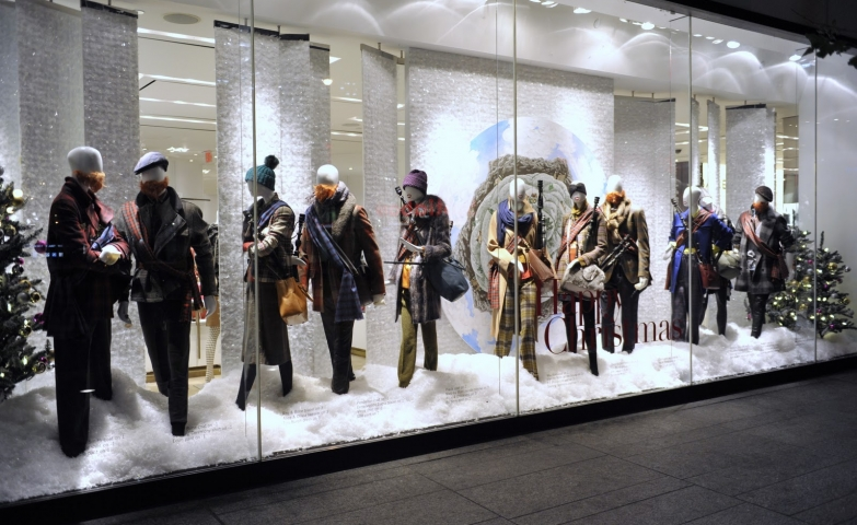 Another Holt Renfrew Christmas window display, with mannequins dressed in different thick clothes, looking like they are on the move and having a conversation.