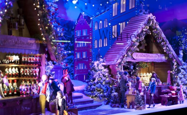 This Christmas window display is including little houses, little waxworks, and all together are creating the image of a marketplace in the holiday time.