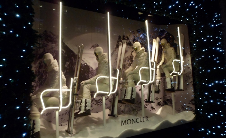 Skiers dressed in a white ski suit, looking futuristic on the chairlift, surrounded by Christmas lights for the window display.