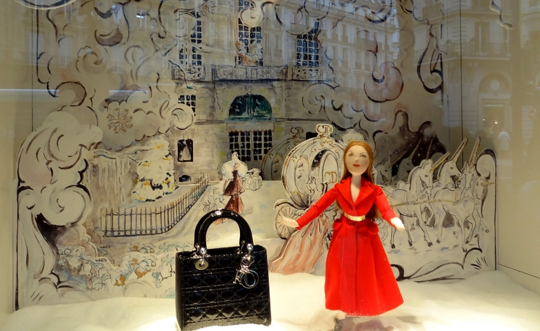 A  window display with a puppet dressed in red, ready for Christmas night, and an elegant bag, near the puppet.