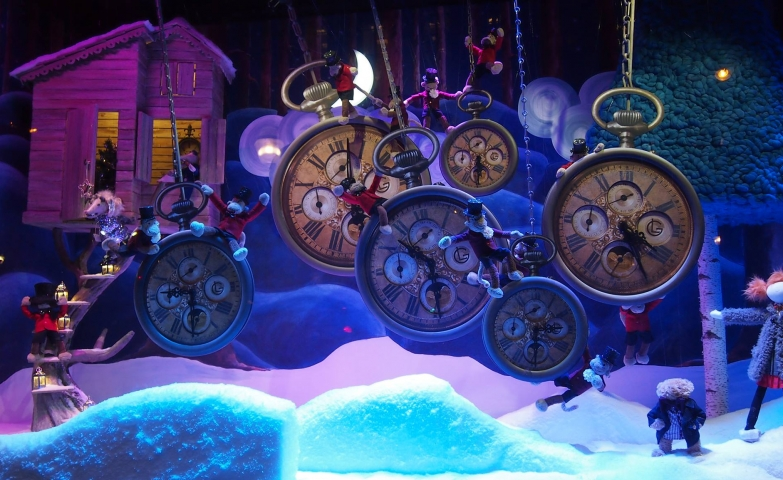 A very rich and sumptuous Christmas window display, with hanging clocks indicating different times, foam snow and puppets.