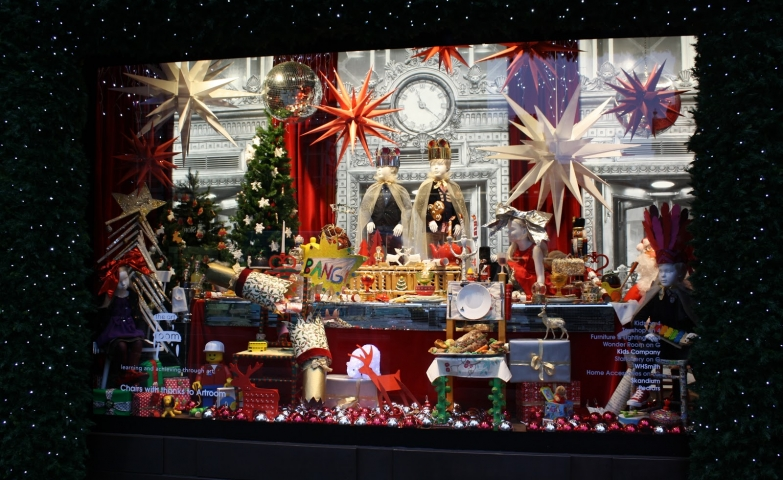 A table with goodies, presents and proper decoration in this Christmas window display.